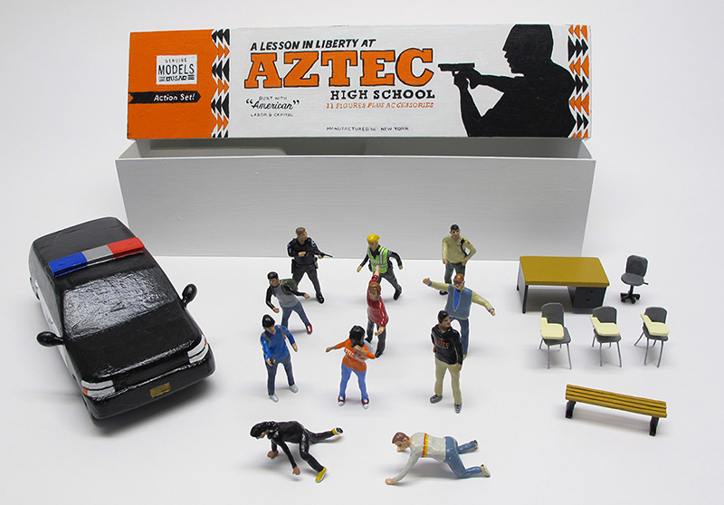 "open box of ""A Lesson in Liberty at Aztec High School"" boxed set containing eleven painted miniature figures, police SUV, and furniture by Matt Ferranto"