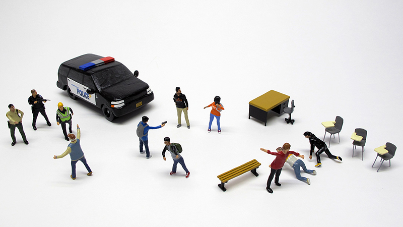 "detail of ""A Lesson in Liberty at Aztec High School"" boxed set containing eleven painted miniature figures, police SUV, and furniture by Matt Ferranto"