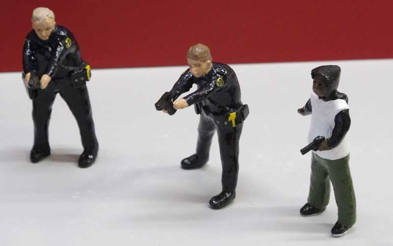 "detail of ""An Incident at Cleveland"" boxed set containing three miniature figures, police car, and bench by Matt Ferranto"