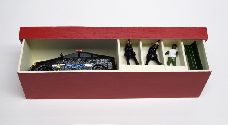 "open box of ""An Incident at Cleveland"" boxed set containing three miniature figures, police car, and bench by Matt Ferranto"