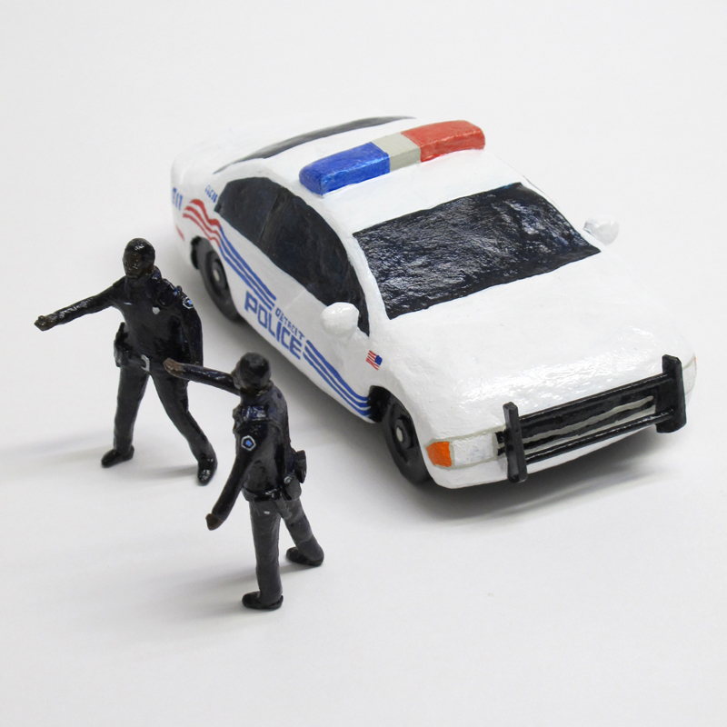 "detail of ""An Incident at Detroit,"" boxed set with three painted figures and police car by Matt Ferranto"