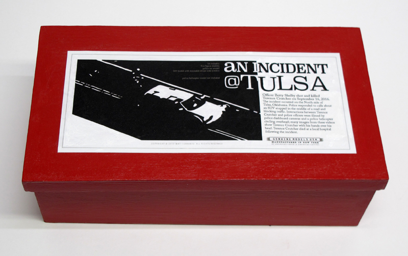 """closed box of """"An Incident at Tulsa,"""" boxed set with five painted figures, SUV, and police car by Matt Ferranto"""