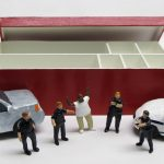 """open box of """"An Incident at Tulsa,"""" boxed set with five painted figures, SUV, and police car by Matt Ferranto"""