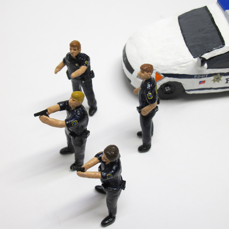 """detail of """"An Incident at Tulsa,"""" boxed set with five painted figures, SUV, and police car by Matt Ferranto"""